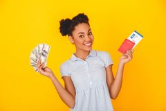 Young african woman isolated on yellow wall studio cute style traveler concept holding money passport and ticket Royalty Free Stock Photo