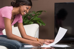 Young african girl learning at home and smiling. Royalty Free Stock Photo