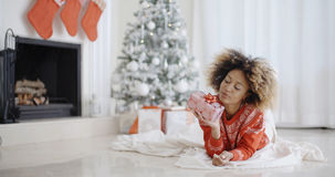 Young African girl lying looking at her Xmas gift Stock Photo