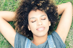 Young african girl relaxing in park. Portrait of young african girl relaxing in park, lying on grass. Closed eyes. Afro hairstyle. Leisure time Stock Photo