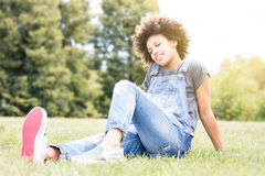 Young african girl relaxing in park. Royalty Free Stock Images