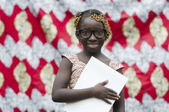 Young african girl with traditional accessories in hair holding paper and looking at camera. Beautiful African Girl Reading Outdoors Royalty Free Stock Photos