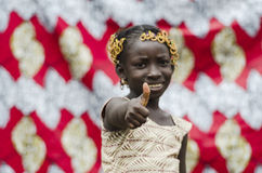 Young african girl with traditional accessories in hair showing thumbs up sign and looking at camera. Beautiful african girl with traditional accessories in hair Royalty Free Stock Image