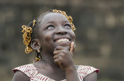 Young african girl with traditional accessories in hair thinking and looking at sky. Gorgeous African school girl thinking isolated Stock Images