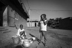 Young African girls washing the dishes in the street of Bamako i Royalty Free Stock Images