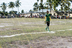 Young african goalkeeper on football field in Zanzibar. Zanzibar, Tanzania - July, 14, 2016: young african goalkeeper on football field in uniform near gate in stock photo