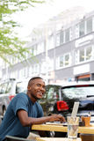 Young african guy at cafe with a laptop. Portrait of young african guy looking away while sitting at outdoor cafe with a laptop on table Stock Image