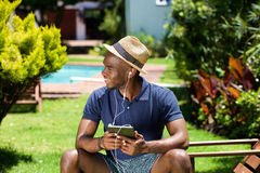 Young african guy listening to music on digital tablet Royalty Free Stock Photos