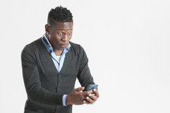 Young african guy looking at cell phone royalty free stock photo