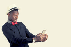 Young african guy looking at cell phone royalty free stock photography