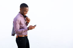 Young african guy reading text message on cell phone Royalty Free Stock Images