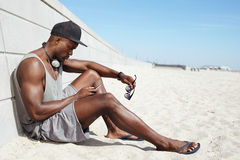 Young african guy sending a text message at the beach. Young guy sending a text message at the beach. African man sitting on beach using mobile phone. Muscular Royalty Free Stock Photo