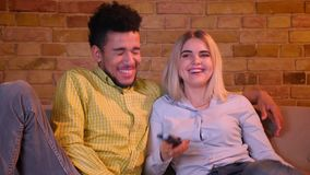 Young african guy strangles his blonde caucasian girlfriend watching TV in cozy home atmosphere. stock video footage