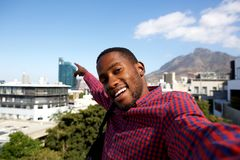 Young african guy taking a self portrait outside. Close up of happy young african guy outside and taking a self portrait Royalty Free Stock Images