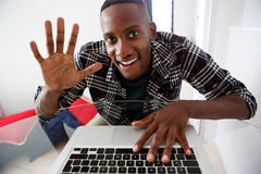 Young african guy video chatting on laptop at home Royalty Free Stock Photos