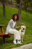Young african lady sitting on bench in park and holding dog Stock Photo