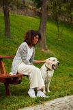 Young african lady sitting on bench in park and holding dog Royalty Free Stock Image