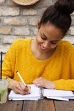 Young african lady sitting at cafe table and writing notes Stock Photos