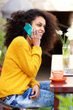 Young african lady talking on cellphone at cafe Stock Photo