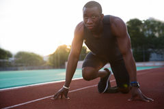 Young african male athlete about to start a sprint race. At the stadium stock photography