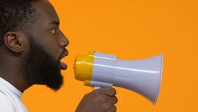 Young african male shouting in megaphone, protest action, speech freedom, leader