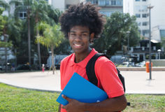 Young african male student looking at camera. Outdoor in the city in the summer Royalty Free Stock Photo