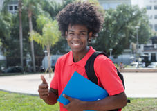 Young african male student showing thumb up. Outdoor in the city in the summer Stock Image
