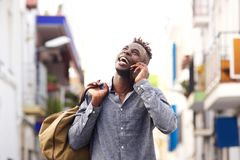 Young african male traveler walking outside talking on mobile phone and laughing Royalty Free Stock Image