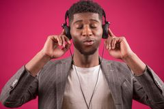 Young African male wearing headphones is mad at music. Isolated on the pink background. hum the song royalty free stock photo