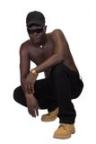 Young african man. Isolated African man, Sierra Leone, black trousers and cap, rapper style Stock Image