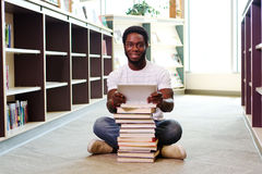 Young African man with books and tablet Stock Image