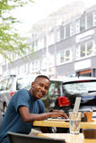 Young african man at cafe with laptop Royalty Free Stock Photography