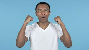 Young African Man Celebrating Success, Blue Background stock video footage