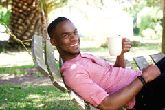 Young african man with a coffee relaxing on hammock Royalty Free Stock Image
