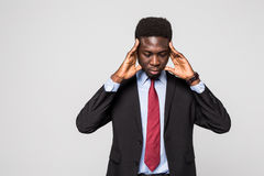 Young African man in formalwear touching his head with hands while standing against grey background Royalty Free Stock Images