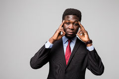 Young African man in formalwear touching his head with hands while standing against grey background Royalty Free Stock Photography