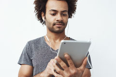Young african man in headphones looking at tablet over white background. Stock Image