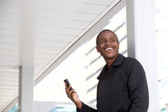 Young african man holding mobile phone and laughing. Portrait of young african man holding mobile phone and laughing Stock Image
