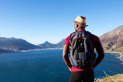 Young african man on holiday. Rear view portrait of young african man on holiday with hat and backpack looking at the sea Royalty Free Stock Images