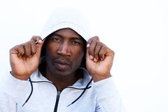 Young african man in hooded sweatshirt. Close up portrait of young african man in hooded sweatshirt against white wall Royalty Free Stock Photography
