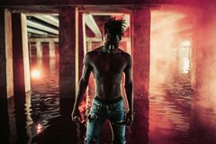 Young African man stands under bridge and holds colored red smoke bomb. Young African man in jeans stands in water under bridge and holds colored red smoke bomb royalty free stock photography