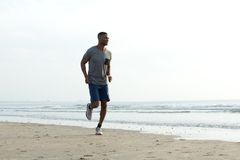 Young african man jogging at the beach Royalty Free Stock Photos