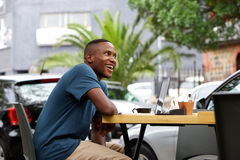 Young african man with a laptop at cafe Royalty Free Stock Image
