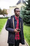 Young african man listening music in big headphones. Student relaxing, dreaming holding smart phone and earphones by hand. Travele stock images