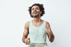 Young african man listening to music in headphones dancing over white background. Stock Photography