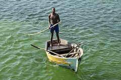 A young african man pilots a simple wooden boat.