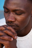 Young african man praying with hands clasped and eyes closed Royalty Free Stock Photography