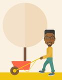 Young african man pushing the cart with tree Royalty Free Stock Photos