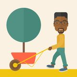 Young african man pushing the cart with tree Royalty Free Stock Image