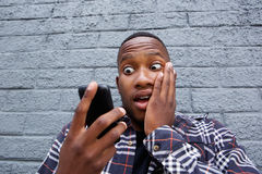 Young african man reading bad message on his mobile phone Royalty Free Stock Image